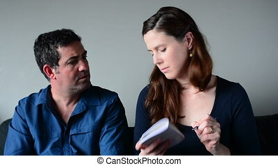 Worried couple listing expenses in the living room. Money...