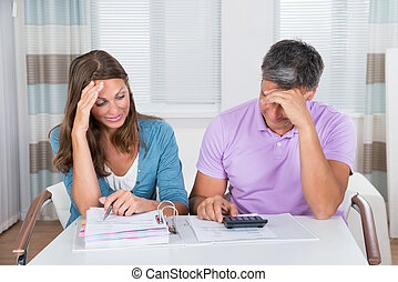 Worried Couple Looking At Unpaid Bills