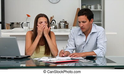 Worried couple paying their bills sitting at a table in the...