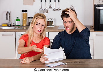 Worried Couple Reading Letter At Home