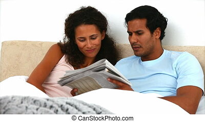 Worried couple reading the news lying on the bed at home