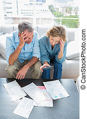 Worried couple sitting on their couch paying their bills