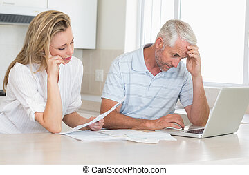 Worried couple working out their finances with laptop at...