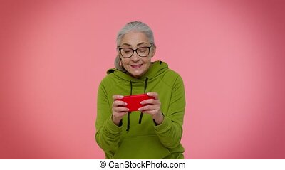 Worried funny elderly good-looking granny woman enthusiastically playing racing video games on mobile phone. Senior old grandmother using smartphone gadget app with drive simulator on pink background