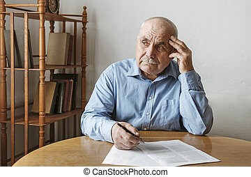Worried elderly man completing a form