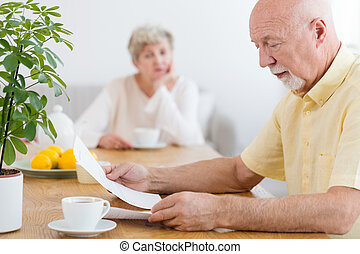 Worried elderly man reading the notification of payment of debt