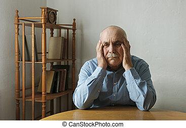 Worried elderly man with his head in his hands