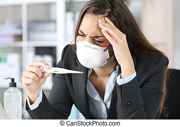 Worried executive with mask looking at thermometer