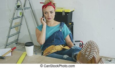 Worried female at workbench talking on smartphone