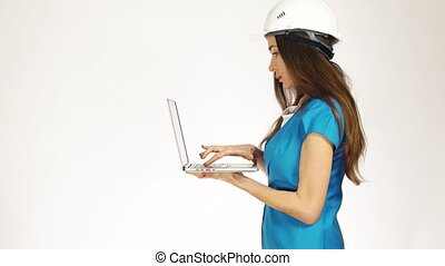 Worried female engineer or architect wearing had hat uses the laptop against white background. 4K clip