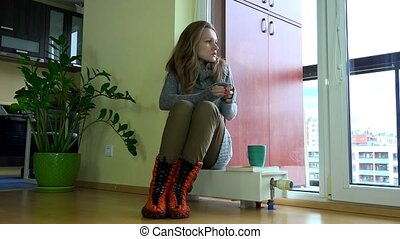 worried frozen woman sitting on radiator with tea coffee cup. Waiting for warming season start.
