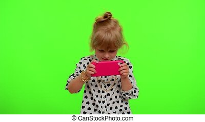 Worried funny addicted teen child girl enthusiastically playing racing video games on mobile phone. Young kid using smartphone gadget app with drive simulator isolayed on chroma key wall background