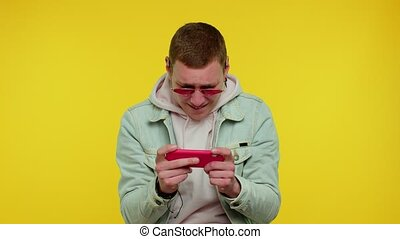 Worried funny addicted teen boy enthusiastically playing racing video games on mobile phone. Young adult man using smartphone gadget app with drive simulator isolayed on yellow studio wall background