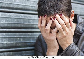 worried girl, hiding her face in his hands, his head bent...