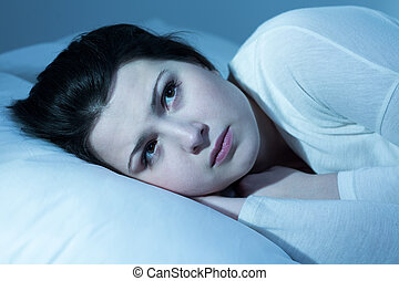 Worried girl in bed - Close-up of young pretty worried girl...