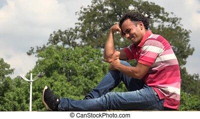 Worried Hispanic Male Sitting And Thinking