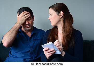 Worried husband and wife listing expenses in the living room...