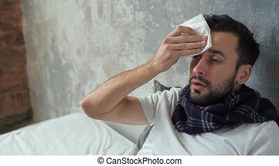 Worried ill man wiping forehead with tissue