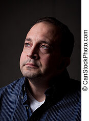 Worried Man - A middle aged man with a contemplative look on...