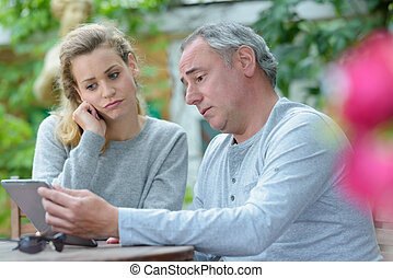 worried man and woman reading some sad news