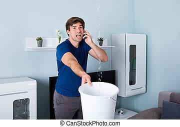 Man Calling Plumber - Worried Man Calling Plumber While...