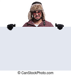 worried  man in winter clothes is holding board