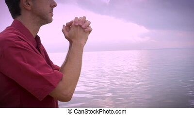 Worried man on beach prays for answers push in shot...