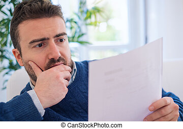 Worried man reading bad news document at home