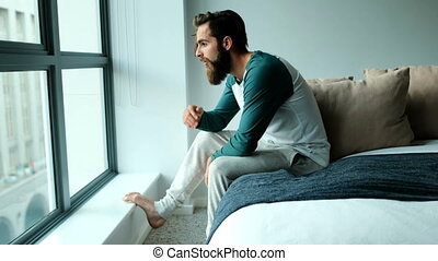 Worried man sitting on a bed 4k - Worried man sitting on a...