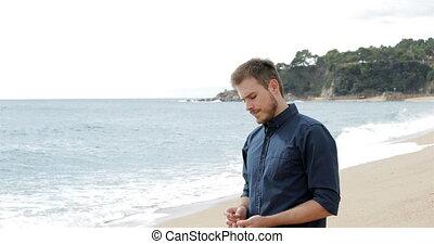 Worried man throwing stones to the ocean walking on the...