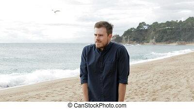 Worried man walking alone on the beach - Worried man walking...
