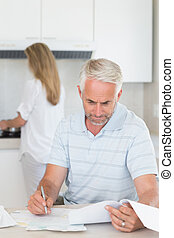 Worried man working out finances with partner standing behind
