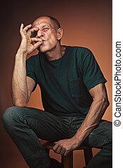 Worried mature man sitting at studio, smoking and thinking...
