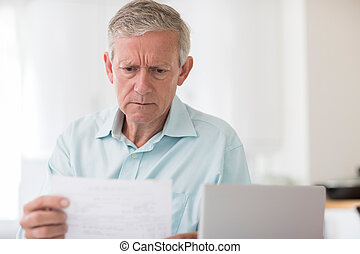 Worried Mature Man With Laptop Calculating Household...