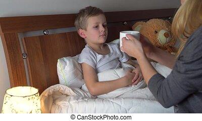 worried mother giving medicine to her sick kid