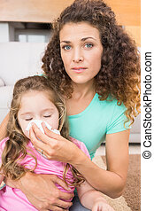Worried mother helping her little daughter blow her nose at...