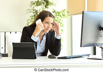 Worried office worker using multiple devices calling on phone