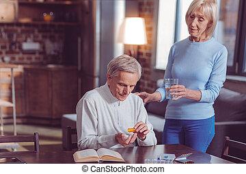 Worried old man taking pills