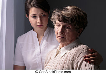 Worried older woman and supportive female carer
