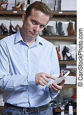 Worried Owner Of Shoe Business With Calculator