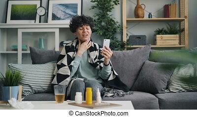 Worried patient talking to online doctor using smartphone...
