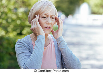 Worried pensioner having headache outdoors