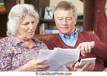 Worried Senior Couple Looking At Bills Together