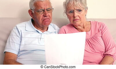 Worried senior couple reading a document at home in the...