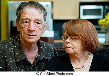 Worried Senior Couple at Home in Modern  Kitchen