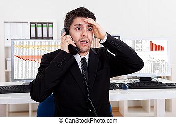 Worried stock broker on the phone