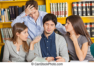 Worried Students With Book Sitting In Library