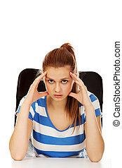 Worried teenage woman sitting behind desk