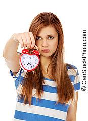 Worried teenage woman with alarm clock