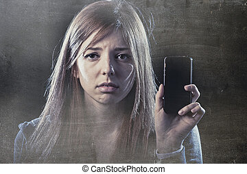 worried teenager holding mobile phone as internet cyber bullying stalked victim abused